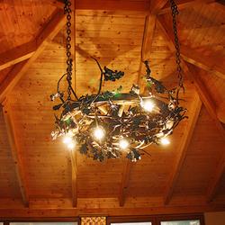 Handgeschmiedeter Eichenkronleuchter in einer Laube – stilvolle Beleuchtung mit Naturmotiv – luxuriöser Kronleuchter