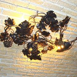 Origineller Kronleuchter mit dem Naturmotiv einer Weinrebe als außergewöhnliche Weinkellerbeleuchtung…