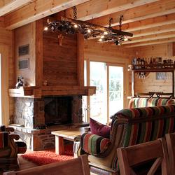 Außergewöhnliche, als in eine Holzleiter wachsende Weinrebe geschmiedete Hängeleuchte am Kamin in einem Wochenendhaus