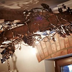 Design-Leuchte am Balken mit Weintraubenmotiv in einem Weinkeller – stilvolle Leuchten