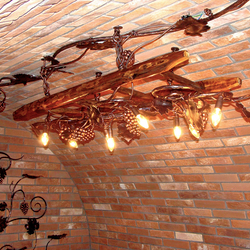 Exklusiver Kronleuchter mit Weinreben-Design an einer Leiter – luxuriöse Lampe in einem Weinkeller